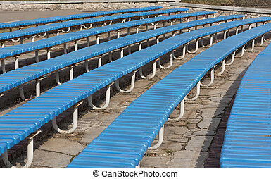 Row of blue wooden seats on a spectator grandstand photo. Bench in the park for the show
