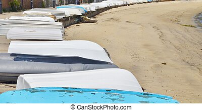 Row of boats lined up on a beach.