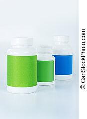 Three bottles of vitamins in one row - Row of bottles. Three...