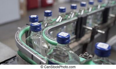 Row of bottles with vodka in conveyor belt in factory production line. Factory for bottling alcoholic beverages. Glass bottles in conveyor belt in distillery production line.