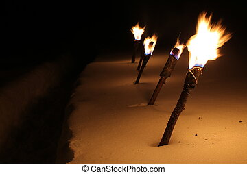 Row of burning torches in the snow