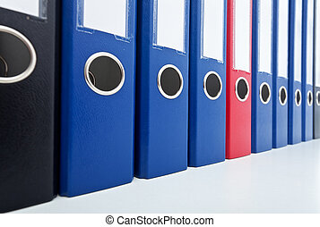 Row of business archive folders - with one prominent red in ...