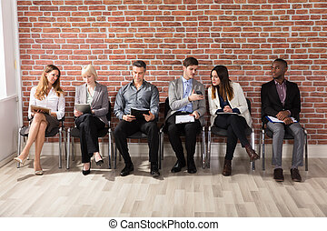 Row Of Businesspeople Waiting For An Interview