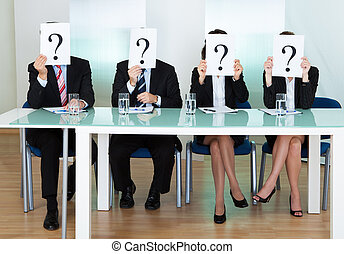 Row of businesspeople with question marks signs in front of...