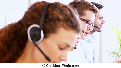Row of call centre agents talking at their desk in the...