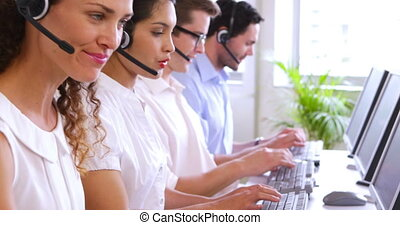 Row of call centre agents typing at