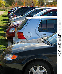 Row of cars in the parking lot on a bright fall day; no logos/trademarks are visible