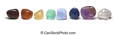 Line of chakra colored tumbled stones on a white background