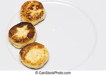 row of cheese pancakes on the white plate. Copy space