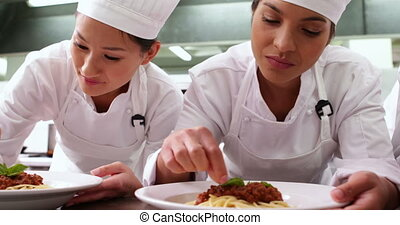 Row of chefs garnishing spaghetti dishes with basil leaf in...