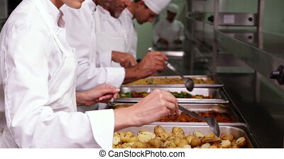 Row of chefs preparing food in serving trays in a commercial...