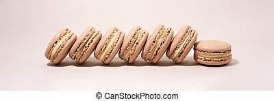 Row of chocolate macarons on the natural background.