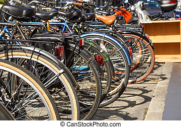 Row of city bicycles parked in a paved street.Selective focus on the first wheel
