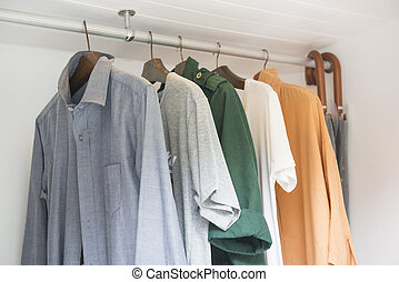 row of clothes hanging in wardrobe