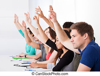 Row Of College Students Raising Hands
