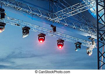 Professional lighting equipment high above an outdoor concert