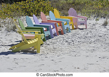 Row of Colorful Adirondack Chairs on the Beach - A row of...