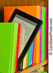 Row of colorful books and electronic book reader on the...