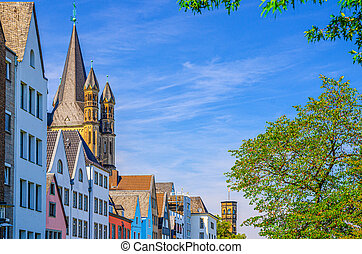 Row of colorful facade buildings, Great Saint Martin Roman Catholic Church tower