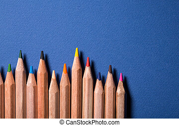 Row of colorful pencils on blue background