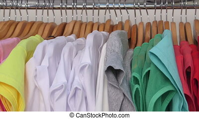 Row of colorful shirts on hangers in a clothing store close-up
