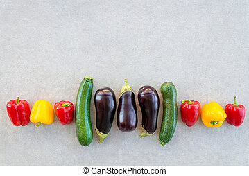 Row of colorful summer vegetables on concrete background