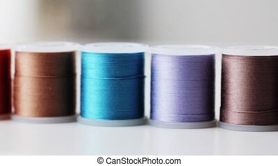 row of colorful thread spools on table - needlework, craft,...