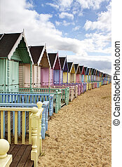 Row of colourful beach huts in rural essex