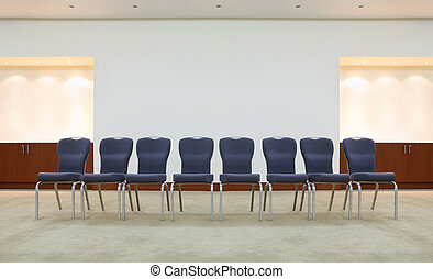 row of comfortable gray chairs in light waiting room; grey ceiling and floor
