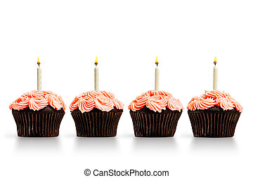 Row of cupcakes with lit candles isolated on white