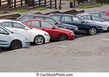 row of diagonally parked cars in the city street