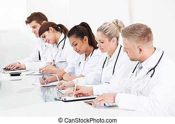 Row Of Doctors Writing At Desk