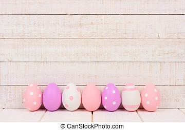 Row of Easter eggs on white wood. Purple, pink and white.