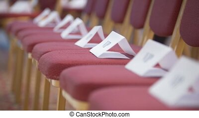 Row of empty chairs in conference hall - signs VIP, close up