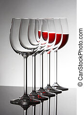 Row of empty wine glassesand one filled at the rear standing on reflective surface