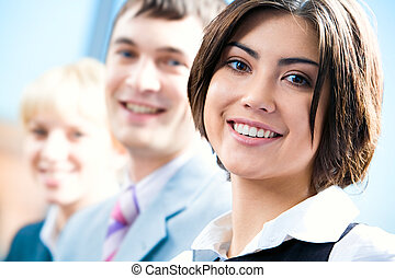 Row of faces of successful professionals with woman in front