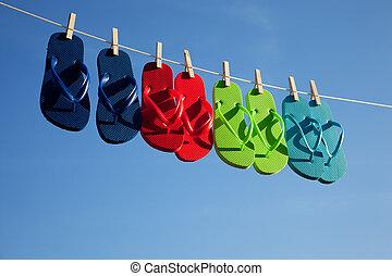 Row of flipflops against a blue sky