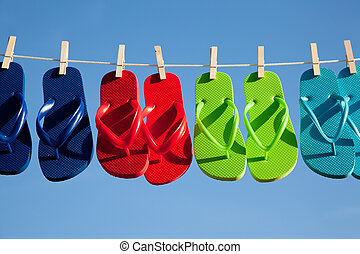 Blue, red, green and turquoise flipflops hanging on a clothesline with a sky blue background