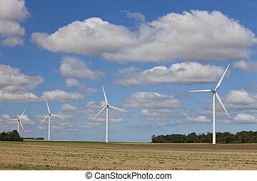Row of Four Green Energy Wind Turbines In a Field - A farm...