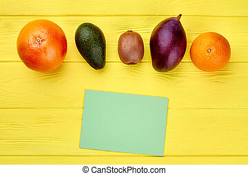 Row of fresh tropical fruits on colorful wood. Assortment of...