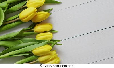 Row of fresh Yellow tulips on white wooden table. Top view,...