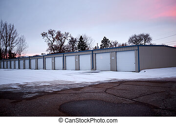 Row of garages in winter snow at sunset