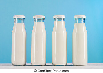 row of glass bottles with milk on tabletop at blue background