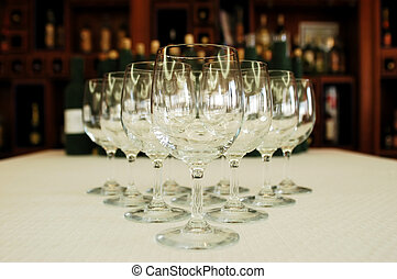 Row of glasses, wine bottles on background