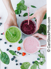 Row of healthy fresh fruit and vegetable smoothies with assorted ingredients. Assorted fruit shakes in hands closeup. Smoothie concept