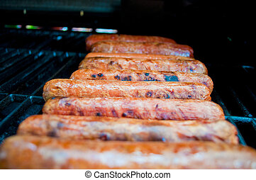 row of hot dogs on grill