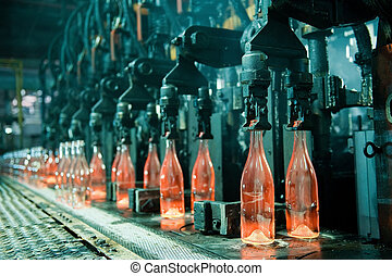 Row of hot orange glass bottles in factory