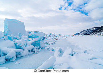 Row of ice blocks and the mountain covering with snow at lake Baikal