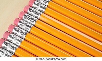 Row of identical sharpened pencils with orange coating....