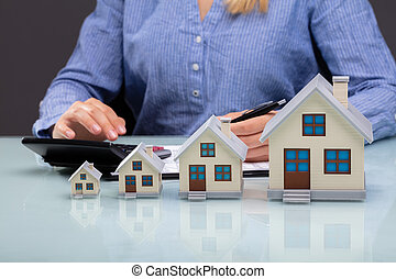 Row Of Increasing House Models On Desk